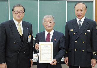征矢雅和区長(左)から賞状を受けた武藤会長(中央、右は鶴見消防署・齋藤俊彦署長)
