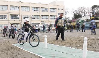 校庭のコースを走る児童