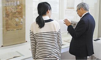 来館者に解説する高田教授(右)