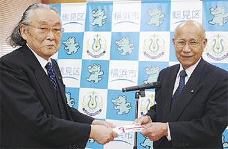 佐藤会長(左)へ目録を手渡す小山委員長