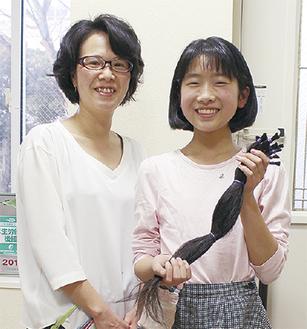 切った髪を持つ紅谷さん(右)と岩本さん