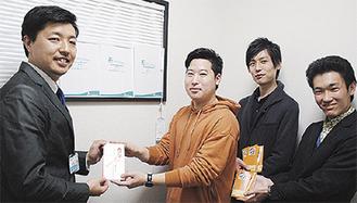 目録を手渡す松村さん(中央、左は須田代表)