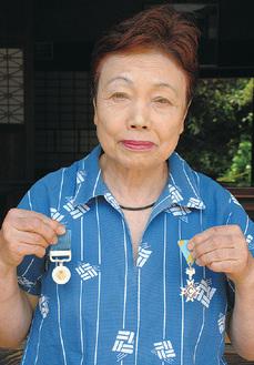 褒章と勲章を手にする新田さん