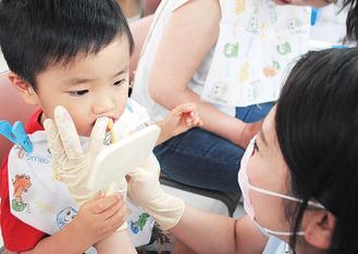 着色した歯を見ながら正しい歯磨きの仕方を教わる子ども
