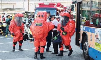 防護服で不審物処理にあたる消防隊員