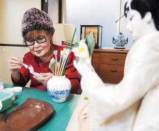 指一本ずつ、塗り方を変えることで艶を出すという根気のいる作業。人形との対話が楽しいと笑う(自宅2階の作業場で)