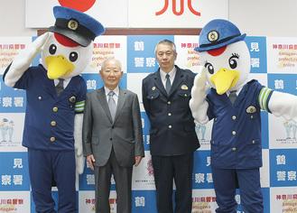 お披露目された着ぐるみと金子会長(左)、中崎署長