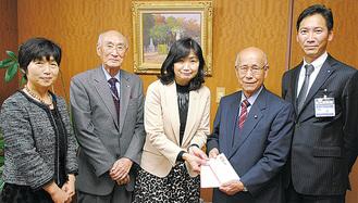 小山副会長(右から2人目)に手渡す榎本部会長(中央)
