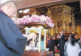 花御堂の釈迦像に甘茶をかける参加者