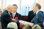 区代表として、セレモニーで記念品を手渡す鶴見区自治連合会の石川建治会長(左)