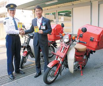 握手を交わす須藤署長(左)、石渡局長と作製されたステッカー