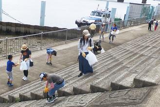 鶴見川河口付近を清掃する参加者ら(写真=キリンビール提供)