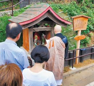 設置後、住民が集まる中でお祓いされた庚申塔と高札(右)