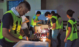 暗い体育館で明かりを準備する参加者