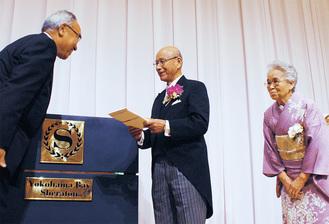 記念品を受け取る小山さん(中央、右は妻・すみ子さん)