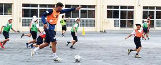サッカーを通じて交流する児童と選手