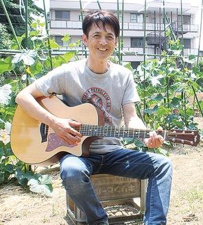 畑でギターを弾く影山さん
