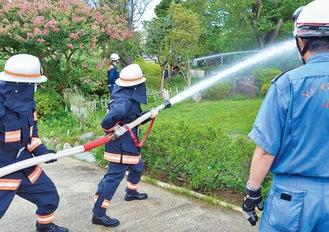 二手にわかれて放水する消防団