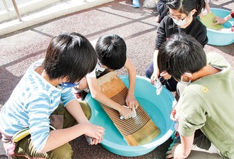 洗濯板で手洗いする児童