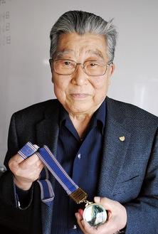 記念のメダルを手にする増渕会長