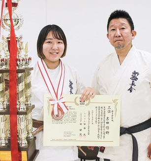 トロフィーと賞状を持ち笑顔の優輝さんと師範の俊浩さん