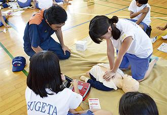 団員の指導の下、心臓マッサージを施す生徒