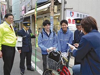 自転車利用者に呼びかける学生ら