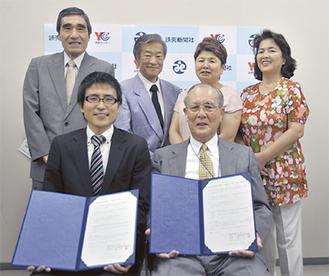 協定書を手にする三藤会長(右)と清水店長