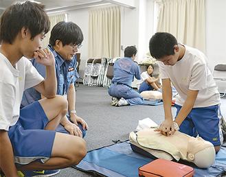 心臓マッサージに挑戦する中学生