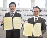 協定書を掲げる渡邉理事長(左)と柴田学長