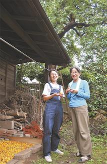 明治期に建てられた物置の前に立つ高野さん(左)と友人