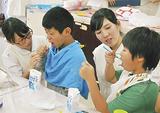 児童にブラッシングの指導をする専門学生