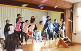 被災地の子どもたちと紙飛行機を飛ばす学生