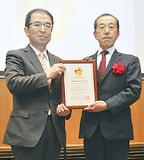 認定証を手にする鈴木社長(右)
