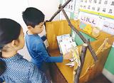 巣箱から本を取り出す児童