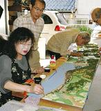 ピンセットで旅籠などを建てる湯川さん(左)ら