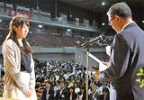 壇上で表彰される教員(左)