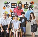 応援旗を前に成田さん(左から2番目)を囲む学校関係者