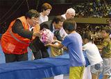 子どもたちから花束を受け取る伊坂理事長(左)ら