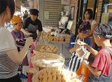買い物客にパンを販売する児童