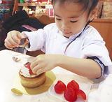 イチゴのタルトにデコレーションする子ども