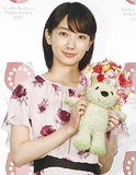 フェアのシンボルキャラクター「ガーデンベア」の人形を手にする波瑠さん