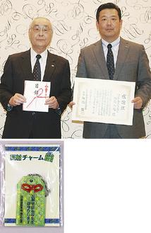 目録を渡す田代総務部長(右)と板橋会長、寄贈された反射チャーム(下)