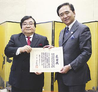 感謝状を手にする伊坂理事長