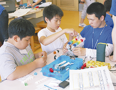 ロボットの組立てに試行錯誤する児童ら