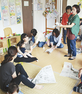 新聞を使ったスリッパ作りを実践する参加者