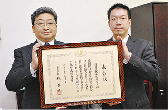 賞状を持つ飯野会長と田川校長
