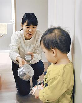 子どもに手洗いをさせようと興味を惹かせる学生