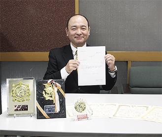認定証を持つ田中本部長