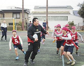 湯原選手とタグラグビーを楽しむ児童たち